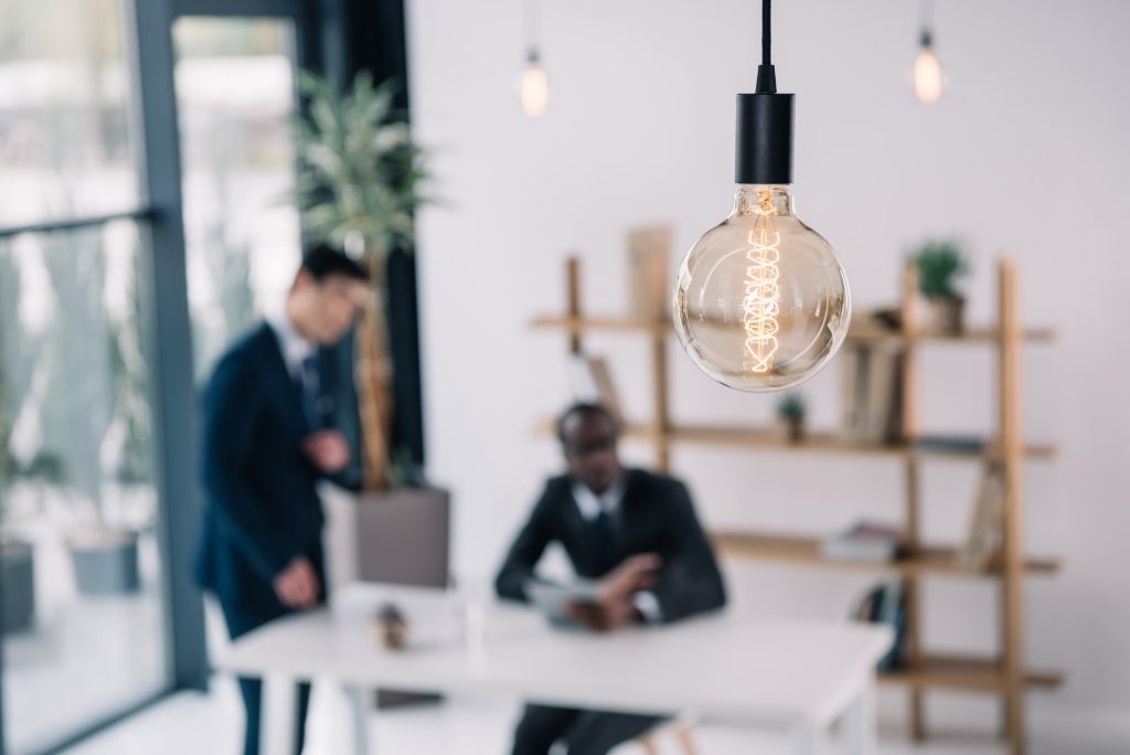 vintage lamp with business colleagues sitting in modern office blurred on background