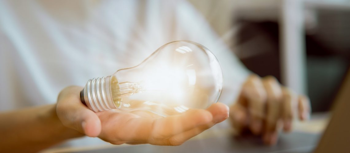 Businesswoman working on laptop and light bulb on the hand with innovative and creativity are keys.